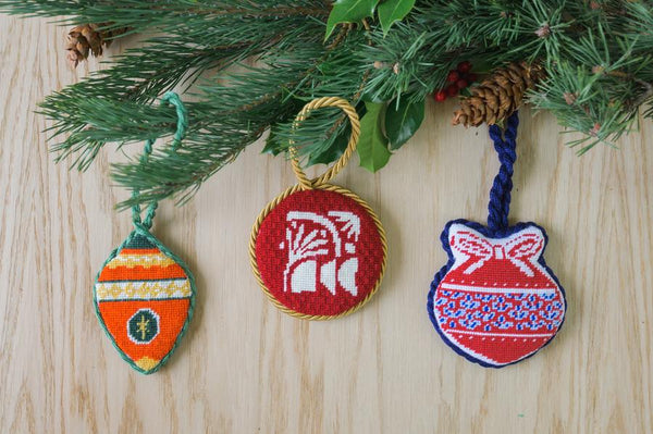christmas needlepoint ornaments hanging in a christmas tree