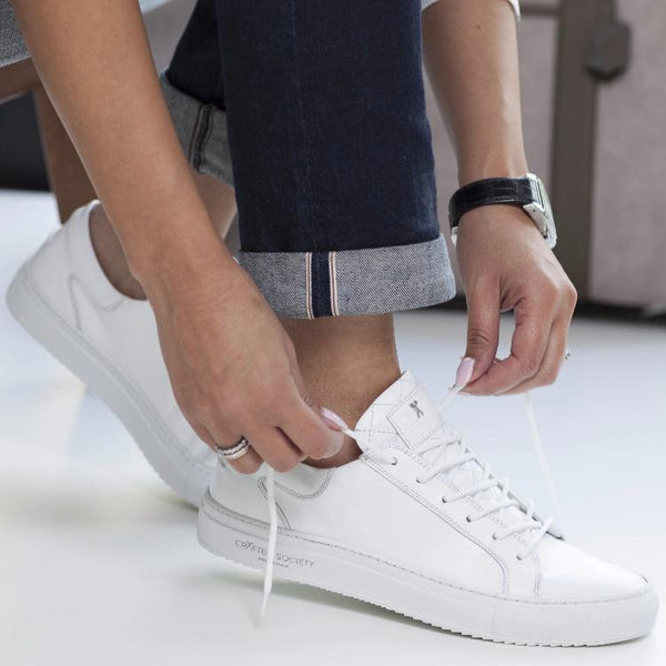 Woman putting on white sneaker