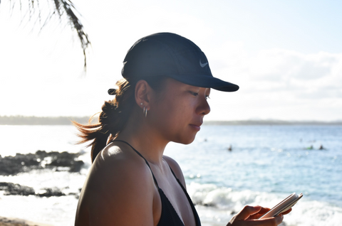 asian girl wearing nike hat at the beach watching phone surfing close up profile photo