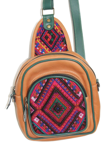 MoonLake Designs Blake Sling Over Backpack Bag in pear tan handcrafted leather with eye catching geometric huipil in shades of pinks and blues featuring dark green leather adjustable strap and multiple easy access pockets perfect for concerts or traveling