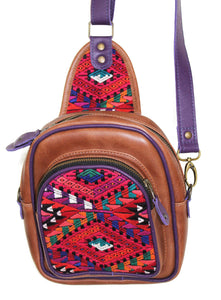 MoonLake Designs Blake Sling Over Backpack Bag in medium tan leather with fun mayan huipil design in pink green orange and red with purple leather adjustable strap and accents and multiple easy access pockets perfect for concerts or traveling