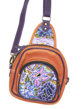 Load image into Gallery viewer, MoonLake Designs Blake Sling Over Backpack Bag in pear tan handcrafted leather with vibrant floral huipil in shades pink and purple featuring dark purple leather adjustable strap and multiple easy access pockets perfect for concerts or traveling