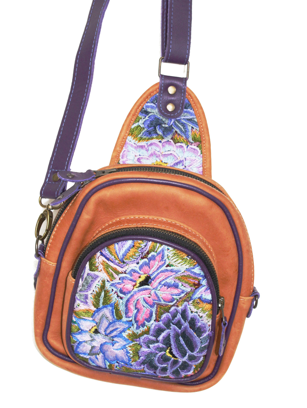 MoonLake Designs Blake Sling Over Backpack Bag in pear tan handcrafted leather with vibrant floral huipil in shades pink and purple featuring dark purple leather adjustable strap and multiple easy access pockets perfect for concerts or traveling