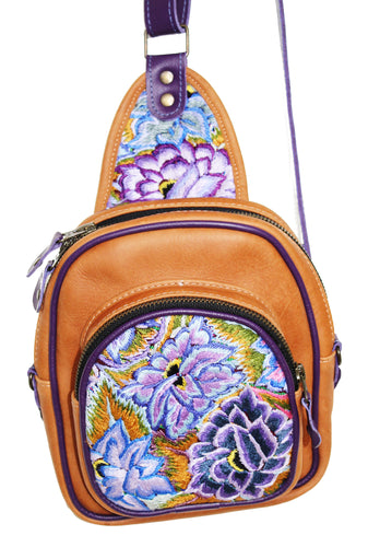 MoonLake Designs Blake Sling Over Backpack Bag in pear tan handcrafted leather with vibrant floral huipil in shades of purple and blue featuring dark purple leather adjustable strap and multiple easy access pockets perfect for concerts or traveling