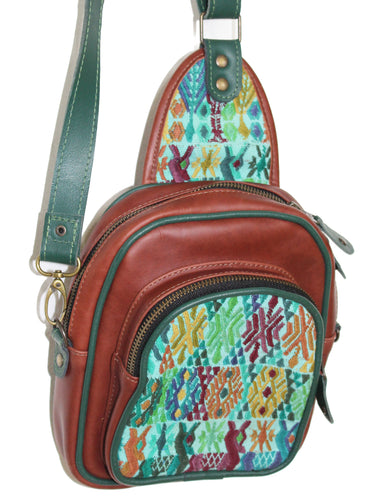 MoonLake Designs Blake Sling Over Backpack Bag in red brown (burnt sienna) with geometric huipil in shades of greens, blues, and complementary colors featuring dark green leather adjustable strap and multiple easy access pockets