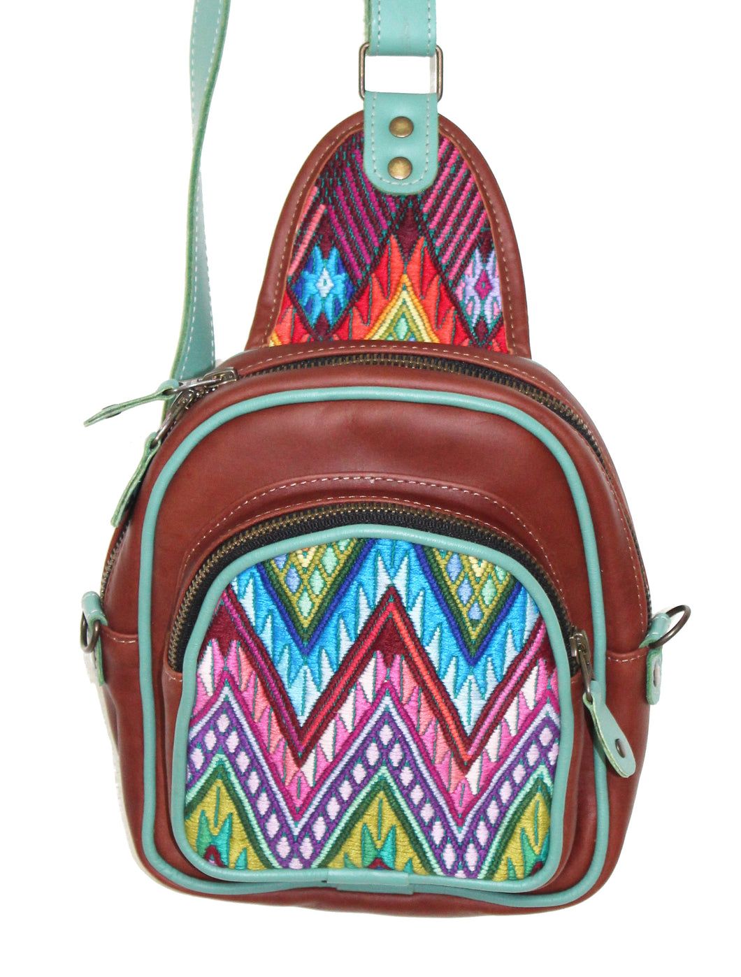 MoonLake Designs Blake Sling Over Backpack Bag in red brown (burnt sienna) handcrafted leather with fun geometric huipil design in blue, pink, purple, and green with teal leather adjustable strap and accents