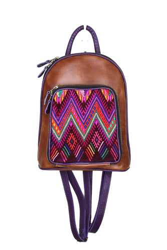 Petite small cute backpack purse in a medium tan leather and purple leather straps and accent. It has double zipper openings. Front pocket has storage for pens and credit cards. Main compartment has two open pockets and a zipper pocket.