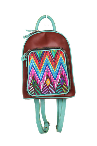 Petite small cute backpack purse in red brown leather and teal leather straps and accent. It has double zipper openings. Front pocket has storage for pens and credit cards. Main compartment has two open pockets and a zipper pocket.