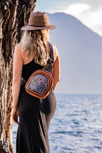 MoonLake Designs Blake sling over backpack with stunning huipil design worn by woman wearing black dress watching the water