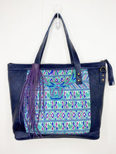 Load image into Gallery viewer, MoonLake Designs Olivia Large Tote Bag in textured navy blue handcrafted leather backview with mesmerizing floral huipil design in shades of blue, teal, and purple and leather tassel zipper closure with metal hardware – purple large fringe tassel sold separately