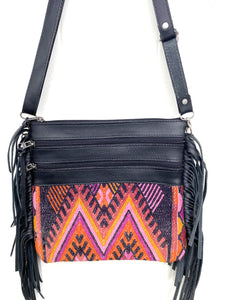 MoonLake Designs Penelope Flecos crossbody bag with fringe in black leather, three zipper compartments, and geometric orange red purple and black huipil design