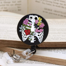 Load image into Gallery viewer, anatomical rib cage badge reel codex anatomicus ribs bones flowers cool unique keys fobs wipeable enamel doctors nurses medical students cord clip back cotton pouch