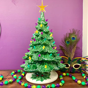 Beautiful vintage ceramic mardi gras tree with fluffy green leaves and purple, green, and gold bulbs. Rests on a white ceramic base with green holly accent. Locally made in Louisiana. Made from a vintage ceramic chrismtas tree mold - new pour.