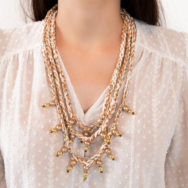 HO NECKLACE IN GOLDEN AND BEIGE THREADS WITH GOLDEN BEATS.