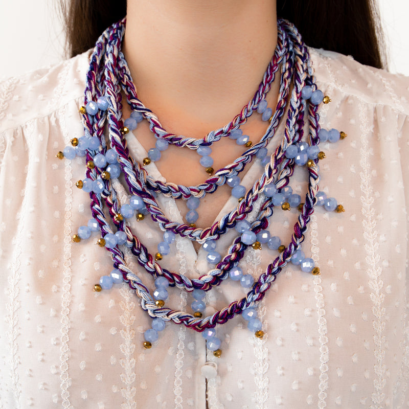 HO NECKLACE WITH PURPLE HUE THREADS AND BLUE BEATS.