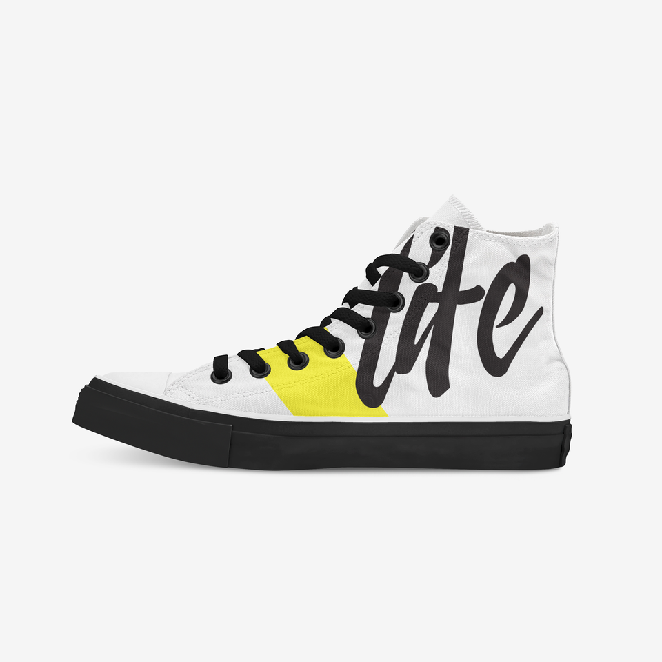 White sneaker view from the inner side. We see the other side of the yellow strip accompanied by three hand-drawn letters. The holes where the black shoelaces are placed are covered with a black metal ring. The shoe sole shows a full black.