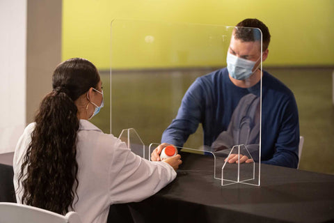 Woman in medical clinic uses an acrylic plexiglass sneeze guard to hand patient information