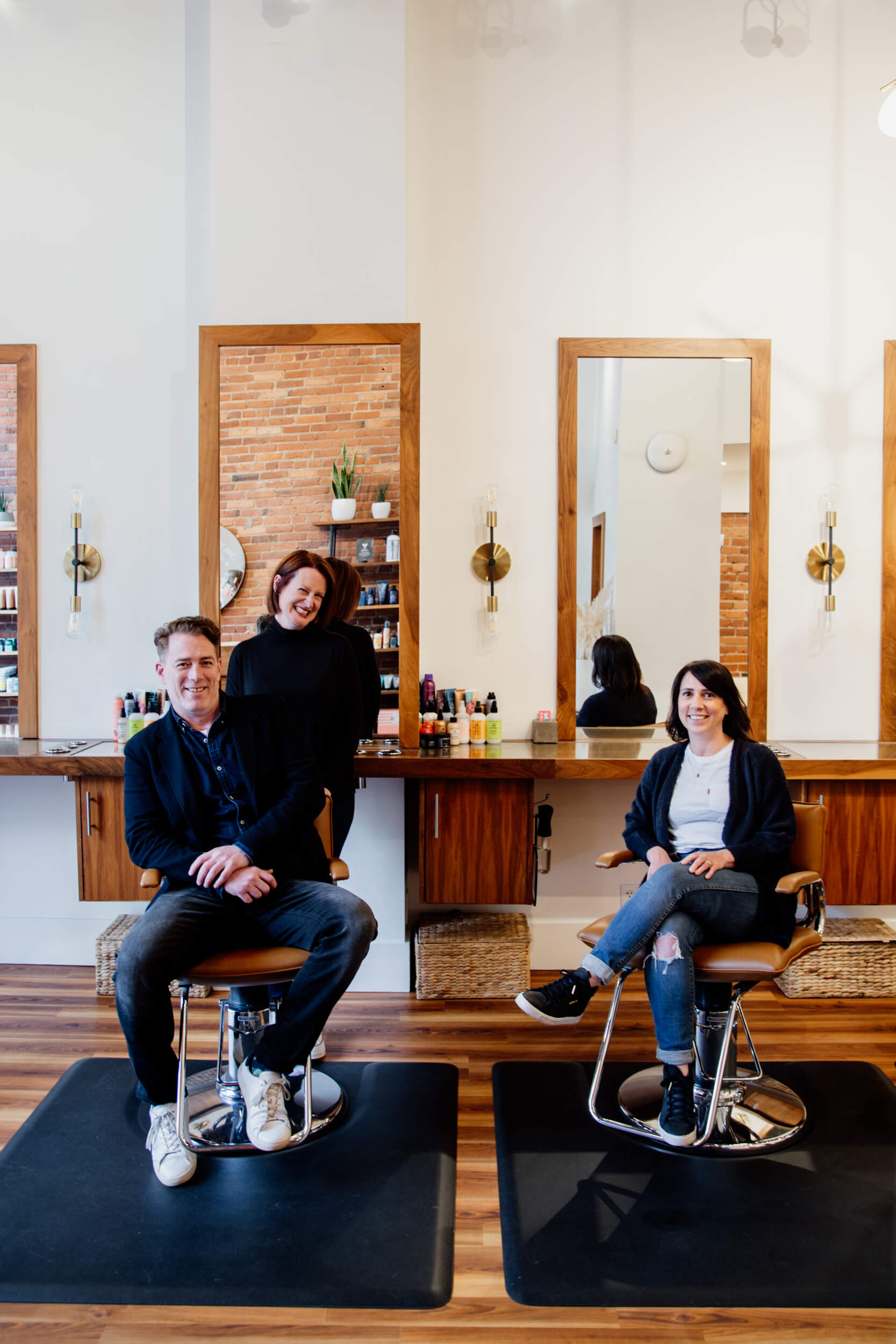 Three people sit in salon chairs and smile.