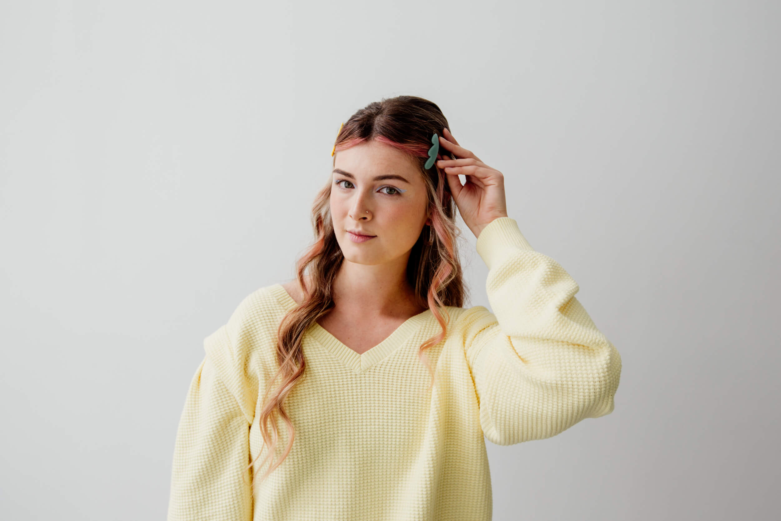 A woman in a yellow sweater pushed her hair back