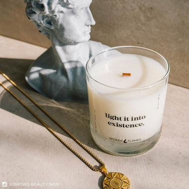 Spoken Flames' Light It Into Existence Candle next to a necklace