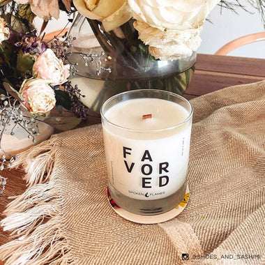 Spoken Flames' Favored Candle on a table next to flowers