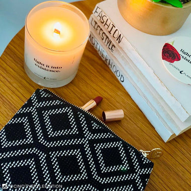 Spoken Flames' Light It Into Existence Candle next to a makeup bag