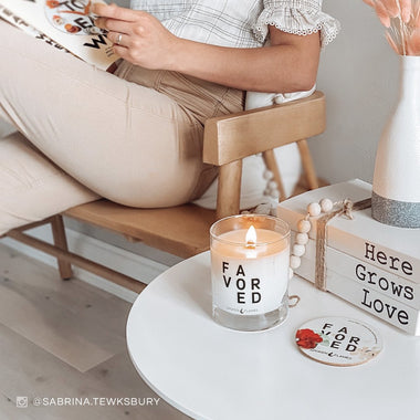 Woman reading book next to a Spoken Flames Favored Candle