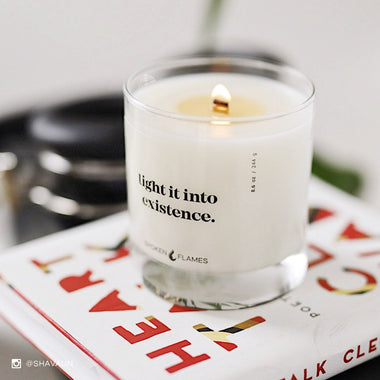 Spoken Flames' Light It Into Existence Candle on a book