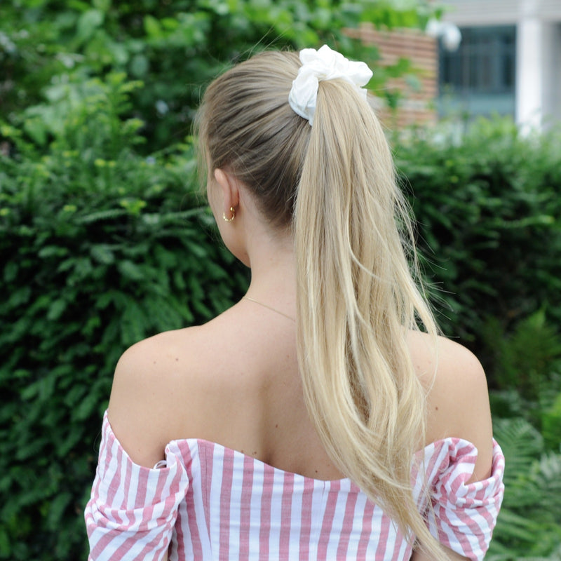 Lady with long blonde hair wearing a Silk Works London ivory silk scrunchie in her hair to form a ponytail. Green trees in background.