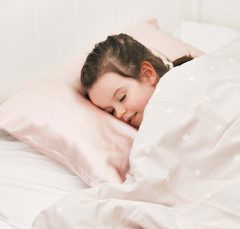 little girl sleeping on a pink silk pillowcase, toddler size