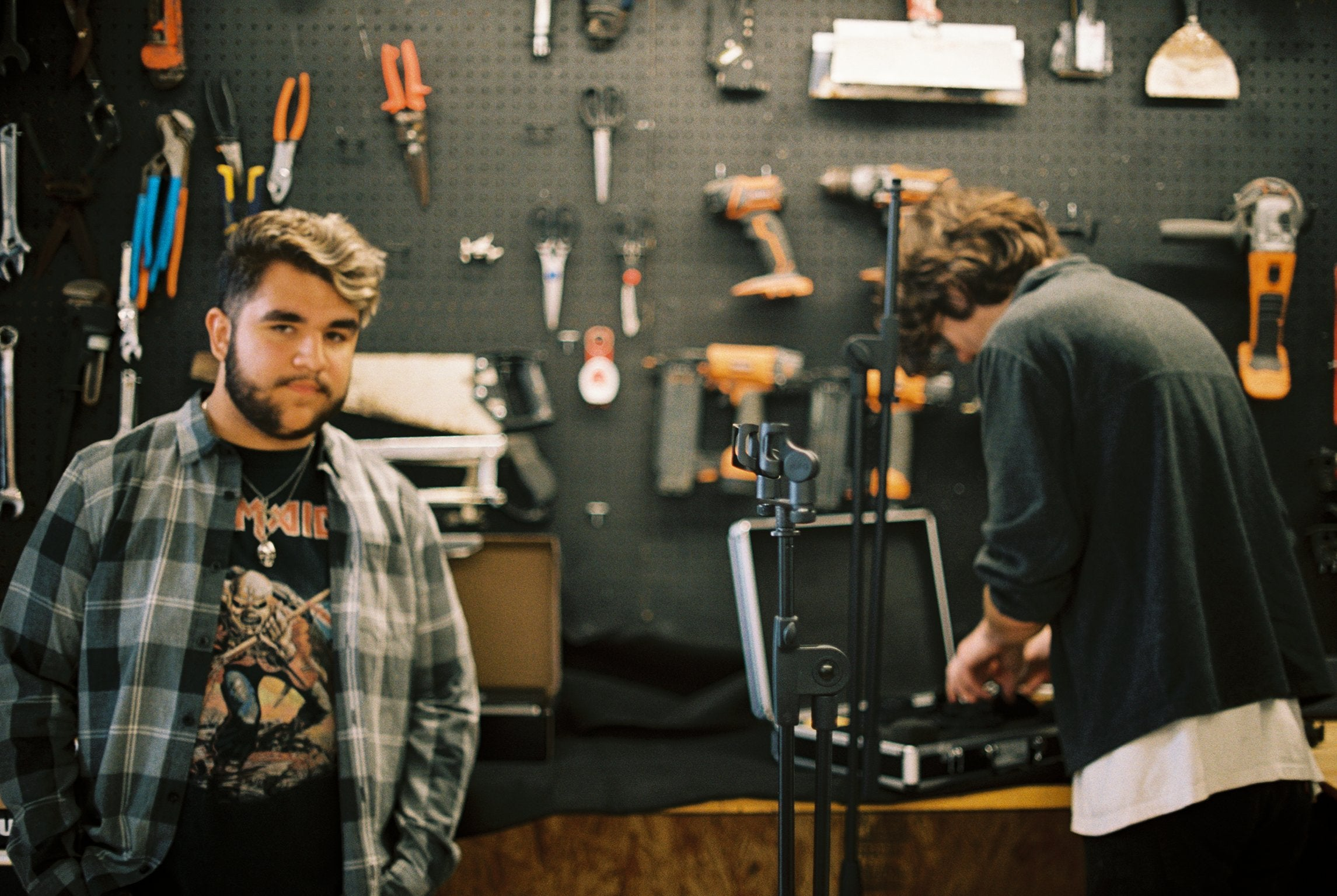 musicians standing in front of a wall of tools.