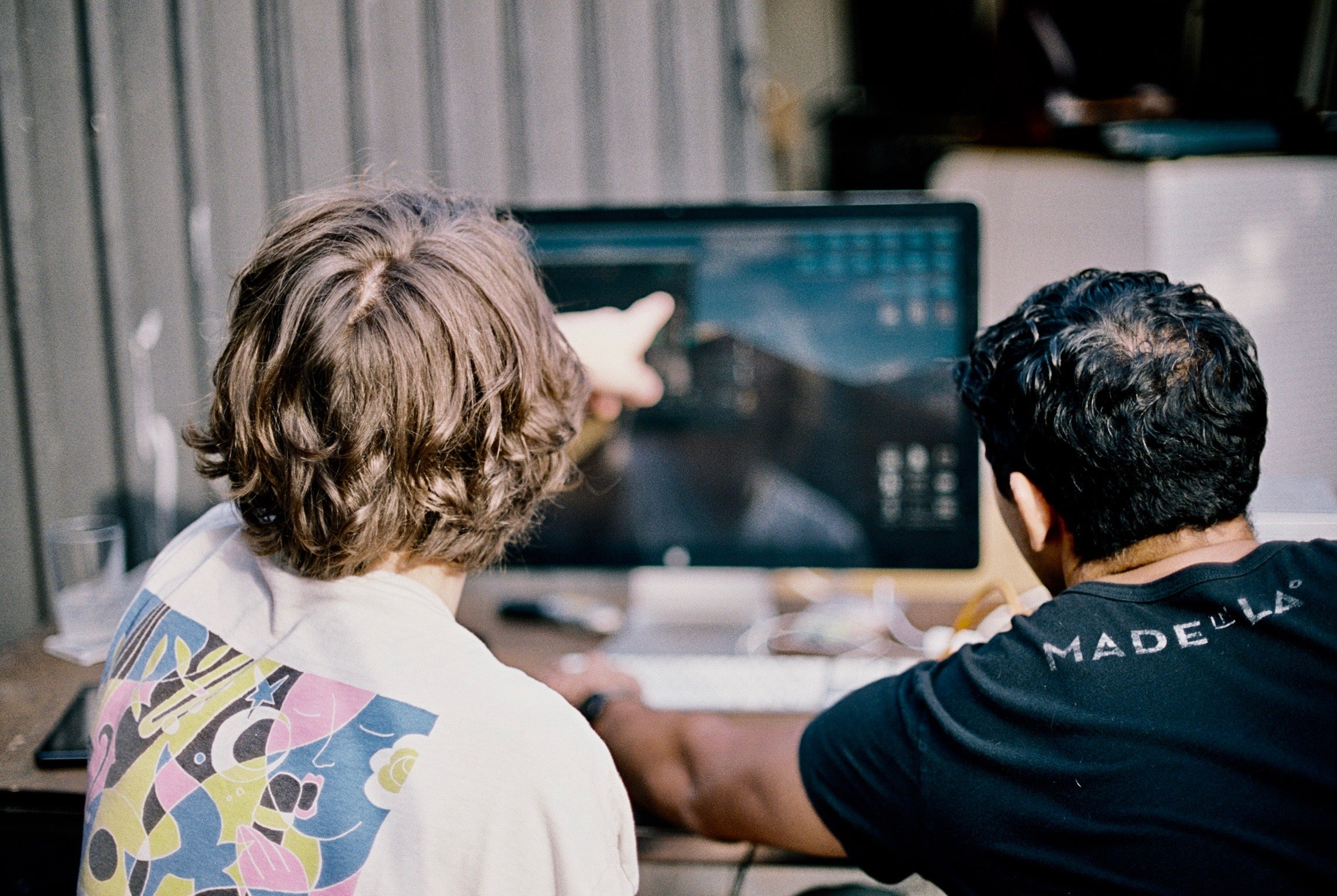 two men in front of a computer displaying music software.