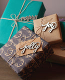 pile of beautifully wrapped christmas presents with calligraphy gift tags