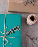 Modern and simple gift wrapping with bakers twine and laser cut christmas gift tag that says merry