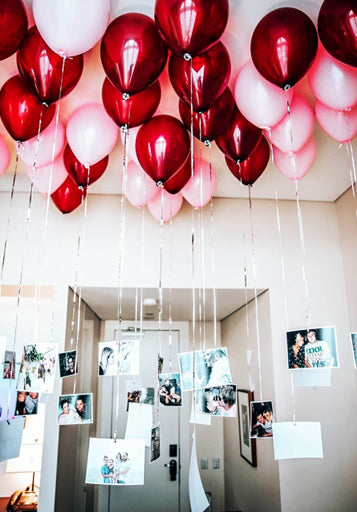Couple's photographs hanging from red and pink balloons