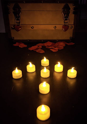 LED tea light candles arranged in the form of an arrow, pointing to a chest locked with two red heart locks, surrounded by red rose petals