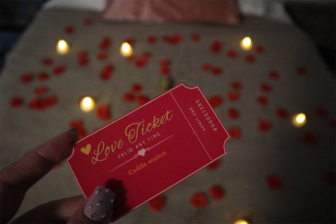 red and gold love coupon that says 'cuddle session' held above a bed covered in rose petals and candles