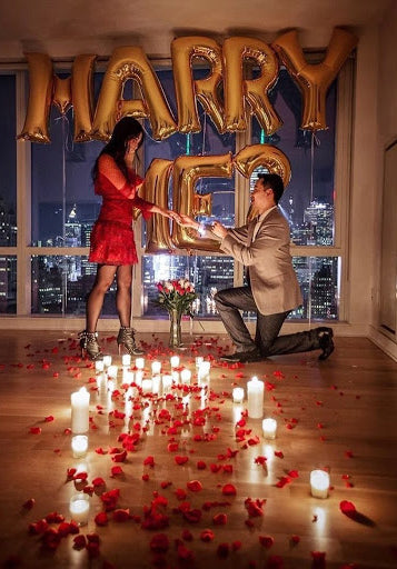 Man on one knee proposing to girl in red dress, in a room with red rose petals, candles on the floor, and balloons spelling 'MARRY ME'