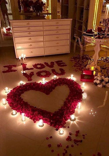 Red rose petals on floor spelling 'I LOVE YOU' and a heart shape made of rose petals, surrounded by tea light candles, on a marble floor
