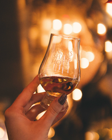 Hand holding an Angel's Share Hotel branded glencairn glass, filled with whisky