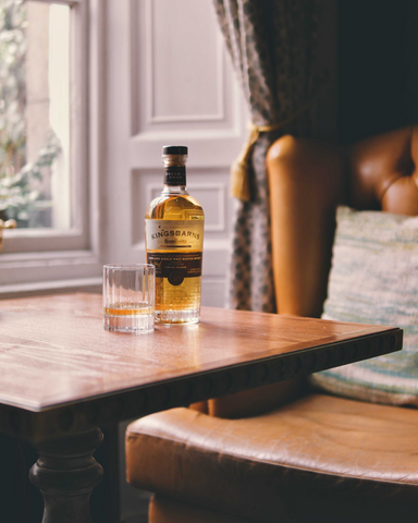 Bottle of whisky on table next to cosy armchair