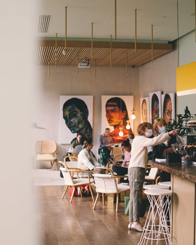 Busy modern cafe with portraits of a woman on the wall