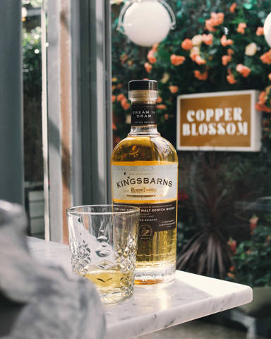 Bottle of whisky sat on a table with a glass
