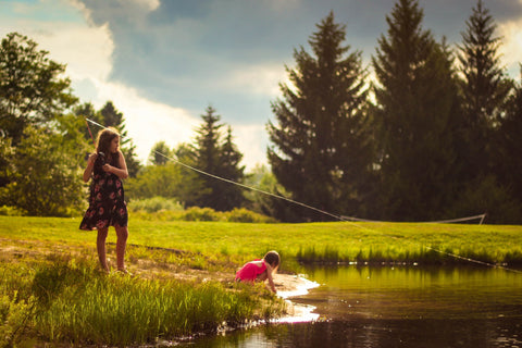 Little girl fishing with her brother in a pond