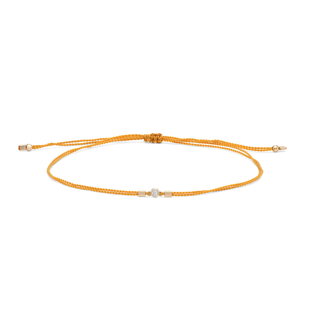 Dainty yellow woven bracelet with a mini diamond and 14k gold accents. The Rode's bracelets are handmade by women in Los Angeles overcoming homelessness.