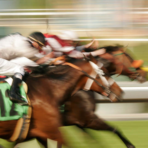Blurred image of running racehorses with riders
