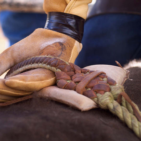 Closeup of cowboy's gloved hand on reins