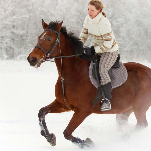 Woman on galloping horse in the snow