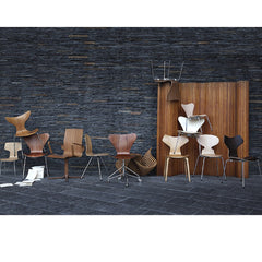 Arne Jacobsen Ant Chair with Arne Jacobsen Chair Collection in Room with Grey Stone Wall Fritz Hansen