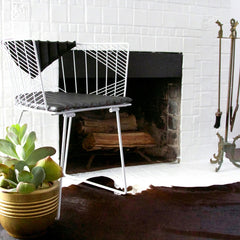 Bend White Captain Chair with Black Bikini Cushion in Room by Fireplace